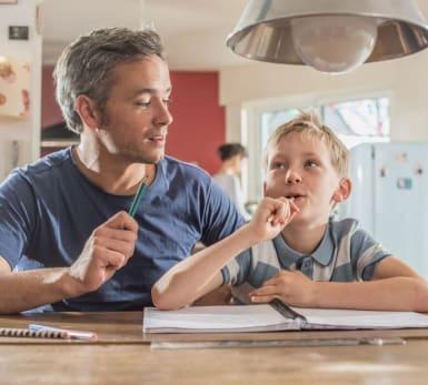 Bild på en äldre man och en yngre pojke som funderar över den senares läxa.