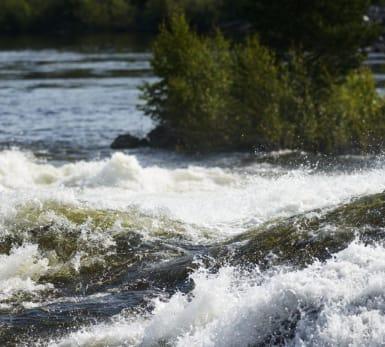 Vatten plaskar våldsamt vid en ström.