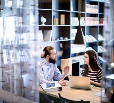 Två studenter sitter och diskuterar vid ett bord. En bokhylla står i bakgrunden. På ett glasfönster syns silhuetter av andra kollegor.