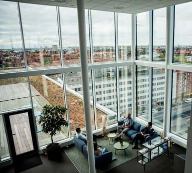 Ovanifrånbild på flera medarbetare som diskuterar inuti en kontorsmiljö.