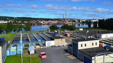 Simsholmens avloppsreningsverk. Stora utomhusbassänger och små fordonsgarage, med Jönköping över sjön i bakgrunden.