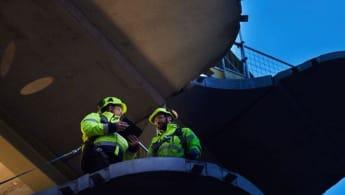 Två NCC-medarbetare står och arbetar vid nya Våghuset, på den plats där fasaden ska fästas.