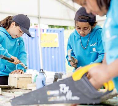 Tre barn snickrar med några mindre projekt som en del av Barnens Byggskola.