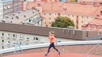 A woman runs at a rooftop running track.