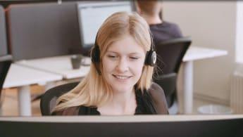 Bild på en kvinna vid en dator som tar emot ett ärende på NCC:s servicecenter