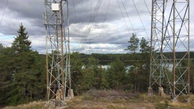 Bild som överblickar en sjö med högspänningsstolpar i förgrunden.