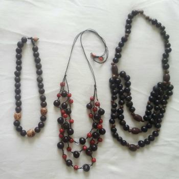 Juego de tres collares  en tonos marrones oscuros, negro yalguno con detalles em rojo.