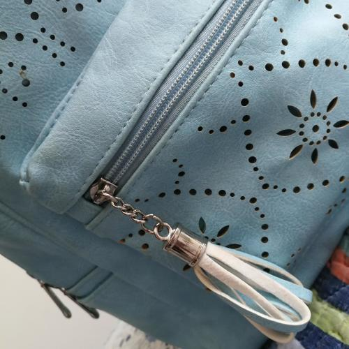 Mochila de color azul claro elaborada con detalles florales.