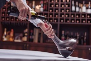 A sommelier decanting wine