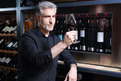 Many studying wine in his glass