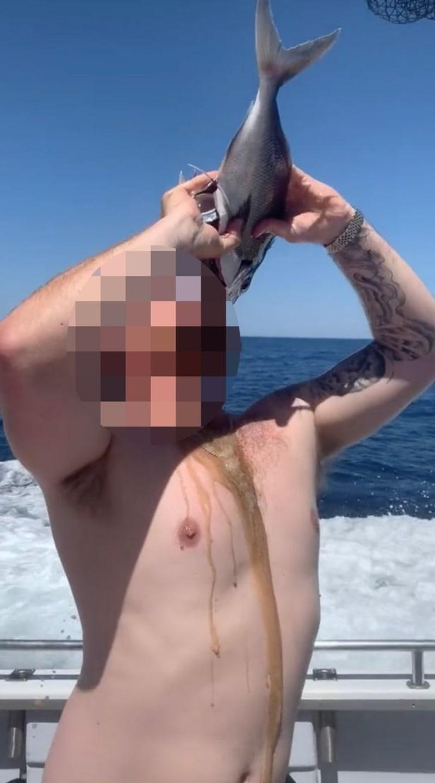 Man Drinks Whiskey Through A Dead Fish (Disturbing Photos)