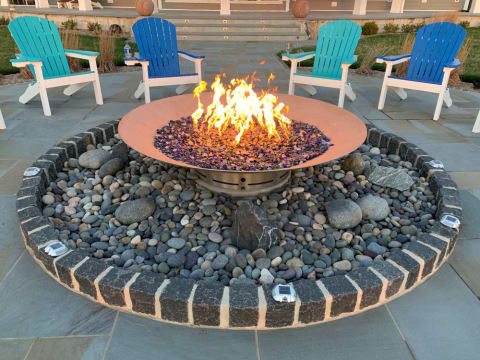 Custom Fire Pit with blue recycled glass, is surrounded by beach pebbles, belgian block and bluestone.