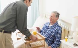 Homme Age d'Or apportant un plateau-repas à une personne âgée