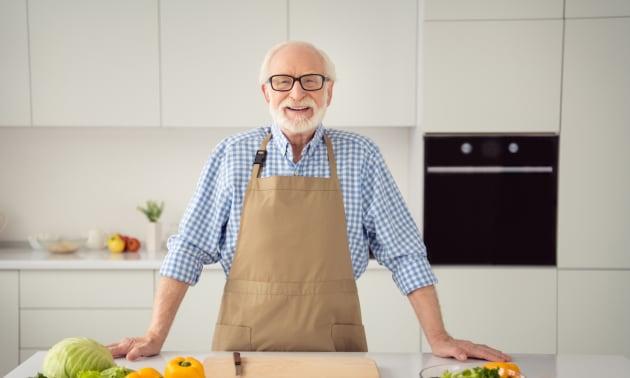 personne agée souriante dans sa cuisine