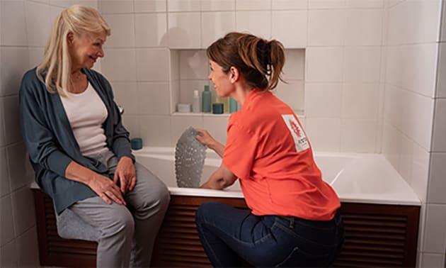 Femme qui essuie une personne âgée avec une serviette