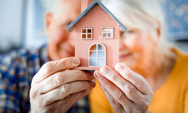 Couple de personnes âgées tenant un porte-clé en forme de maison