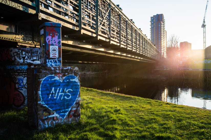 "Bow Locks Railway bridge, with a blue graffiti heart reading ""NHS"""