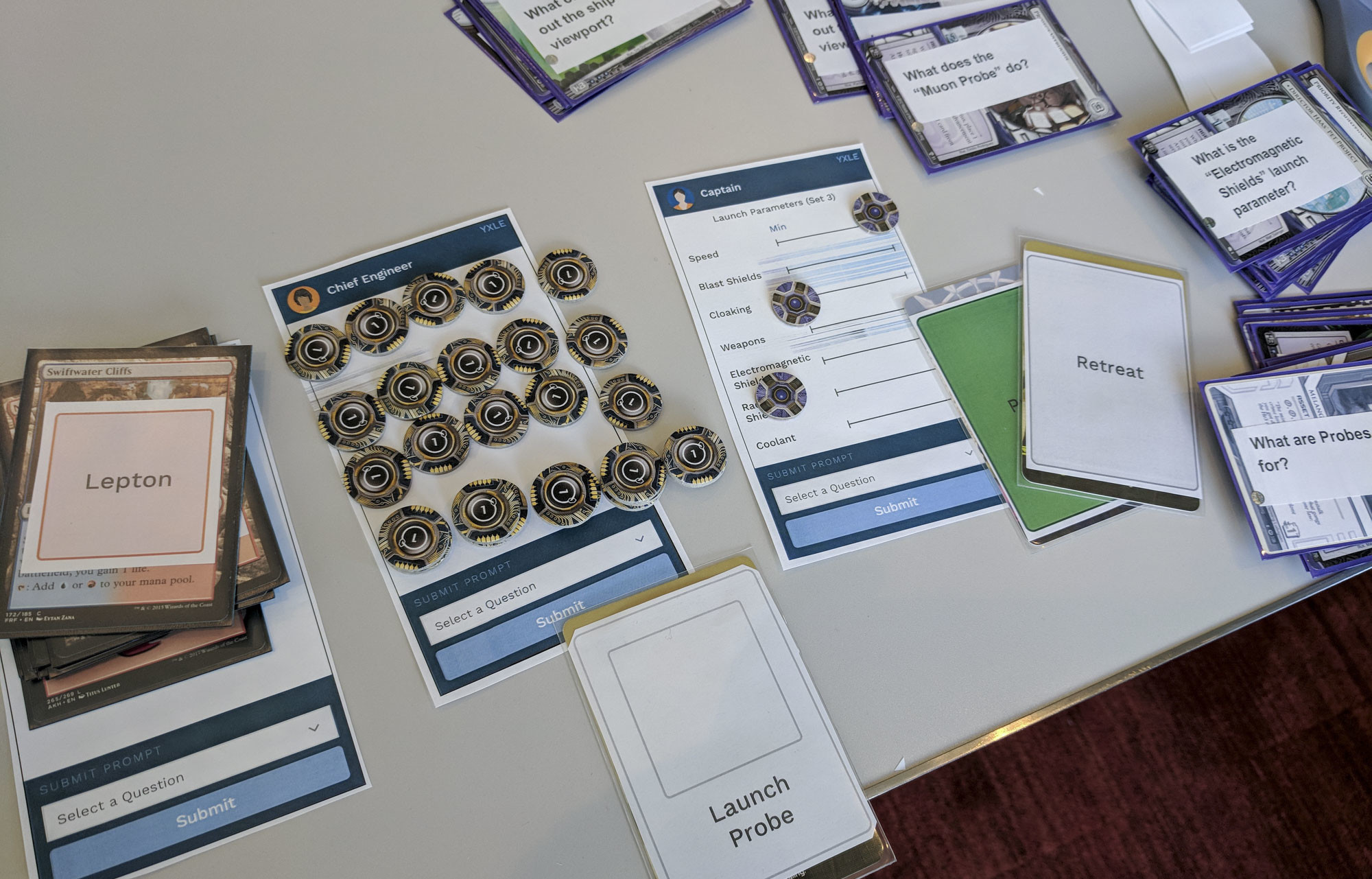 Paper prototypes and repurposed board game tokens used during the first play test.