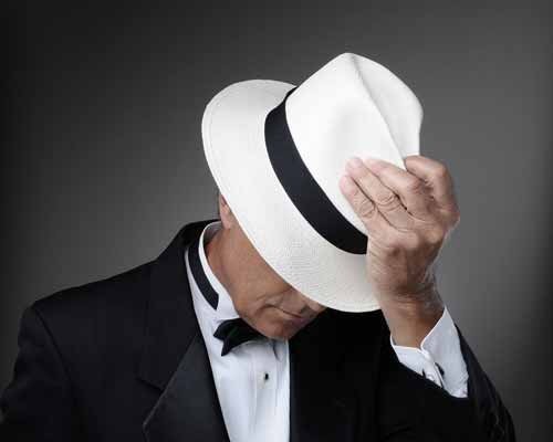 man in a tuxedo and a panama hat
