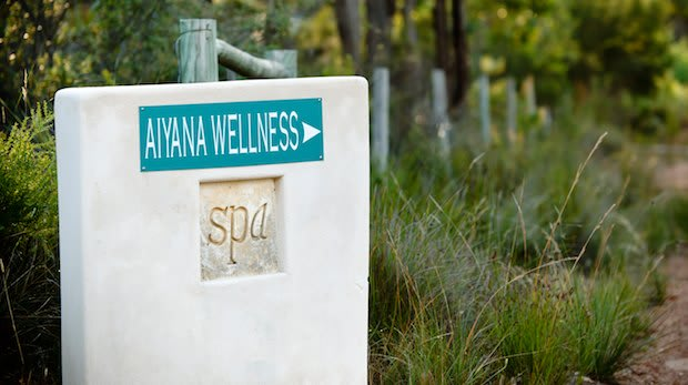 Handmade rendered wall with a sign pointing to Aiyana Wellness centre in front of a country path.