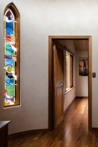 A wooden doorway leading to a bedroom with a stained glass window in the wall