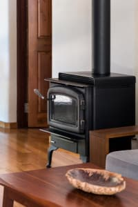 A slow combustion fireplace on a wooden floor