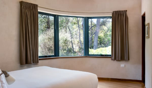 White bed spread with a view into the forrest