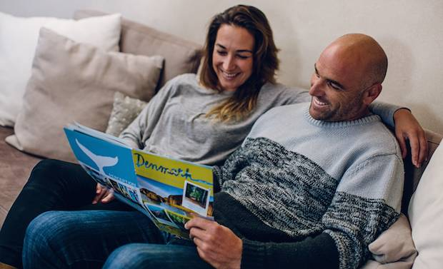 A couple sitting on a couch reading a brochure on Denmark