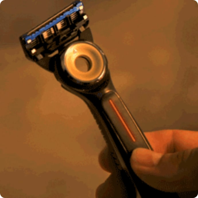 Hand holding Heated Razor with thumb pressing the power button located in the middle of the razor's handle.