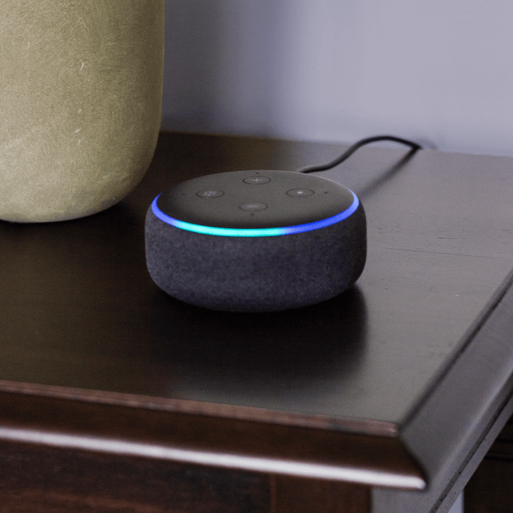 Amazon Echo Dot device on a coffee table ready to interact with voice commands.