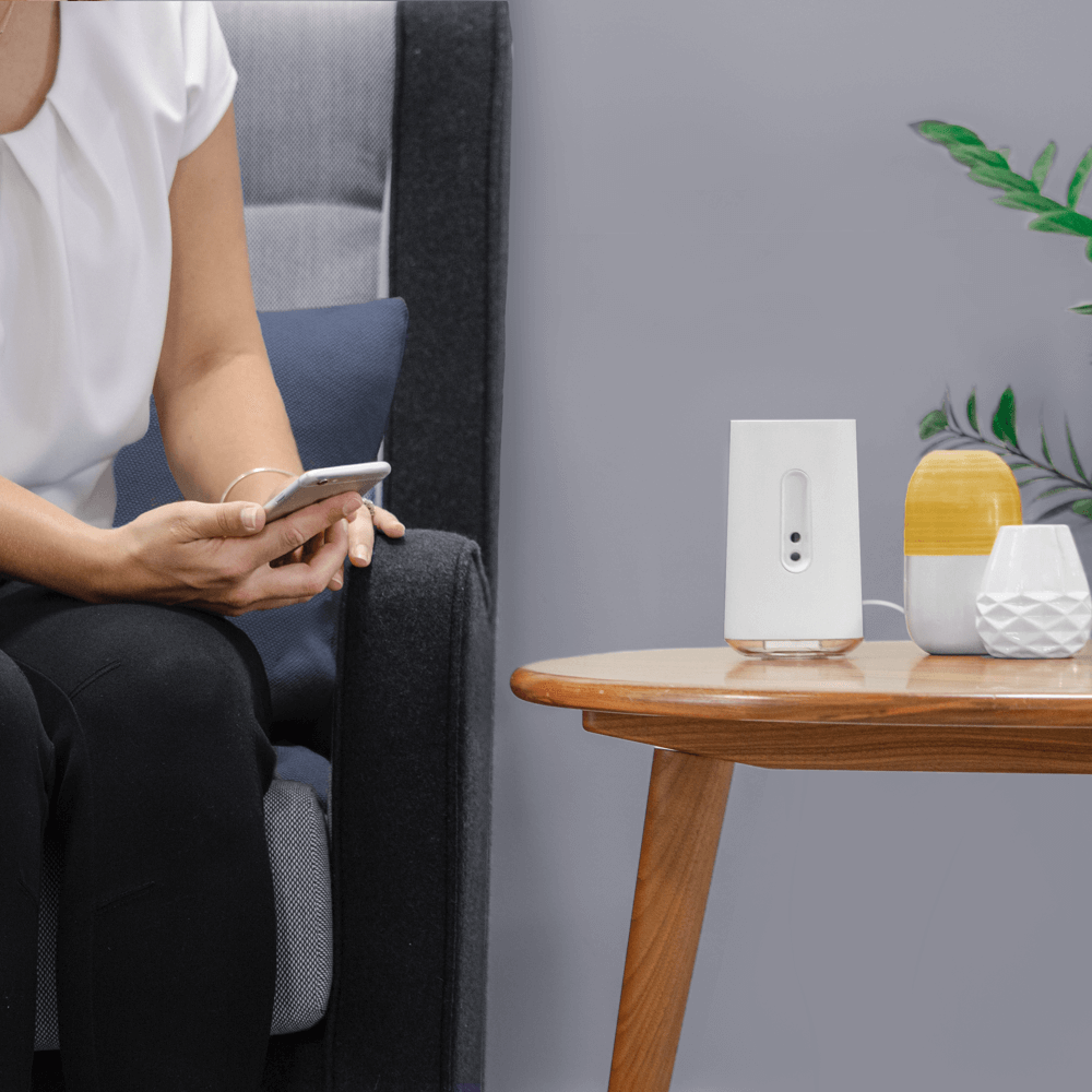 A person sitting near their AIRIA controlling the device over Wi-Fi through the companion app on their smartphone.