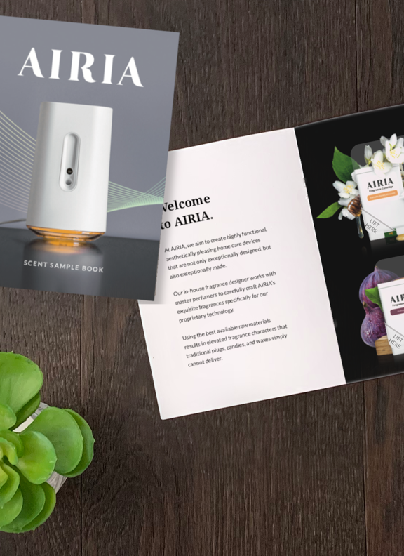 AIRIA scent sample booklet on a wooden table.