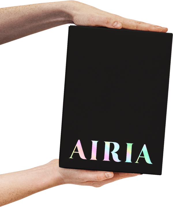 AIRIA device in its package held between hands. The packaging is a rectangular black box showing the AIRIA brand.