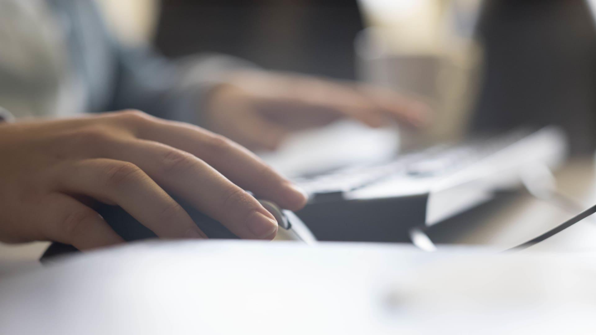 Hände auf der Tastatur und Maus eines Computers