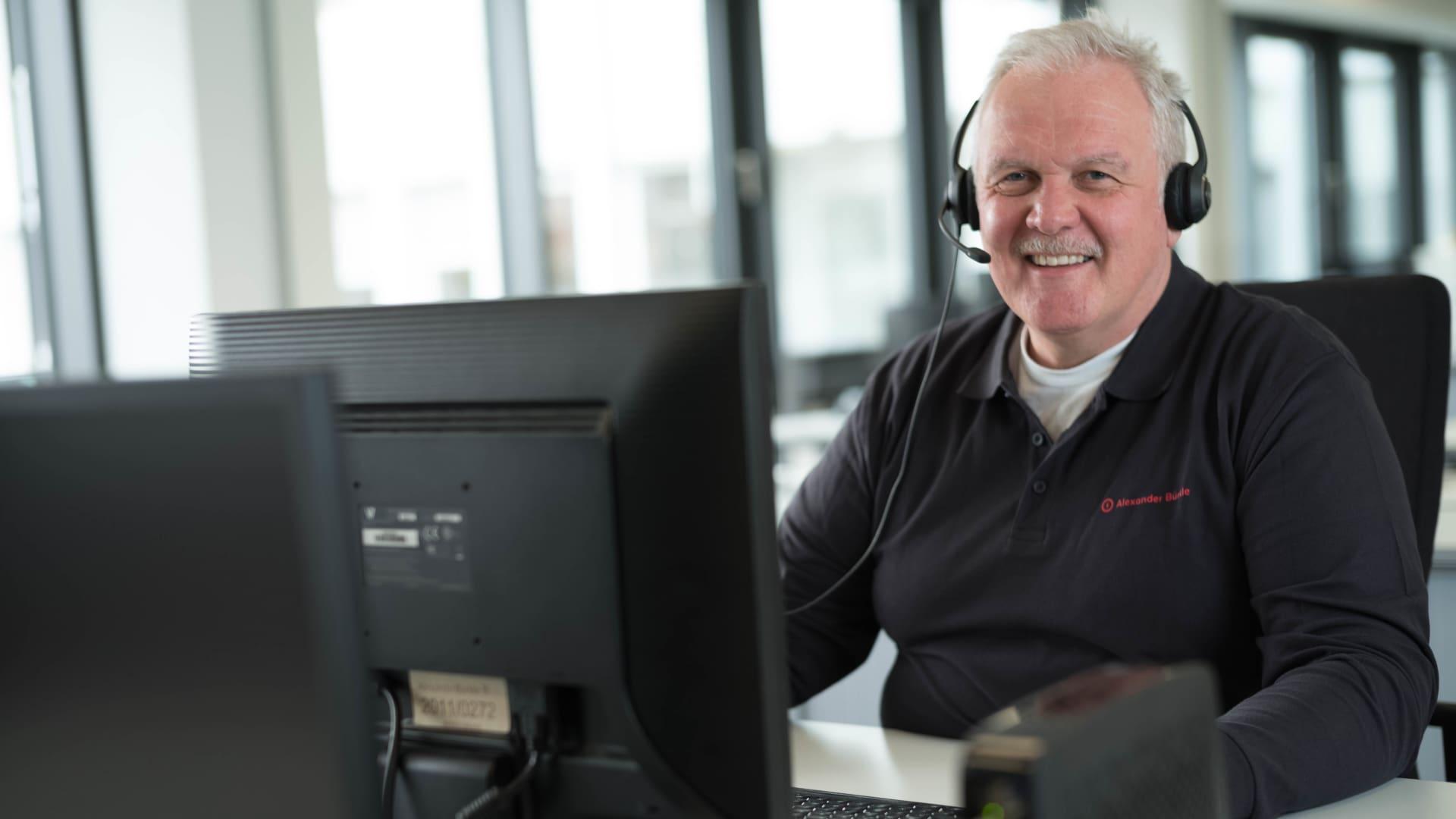 Mann mit Headset sitzt am PC