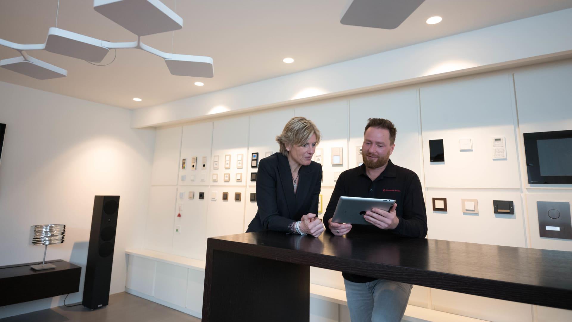 Mann berät Frau mit einem Tablet in einem Verkaufsraum