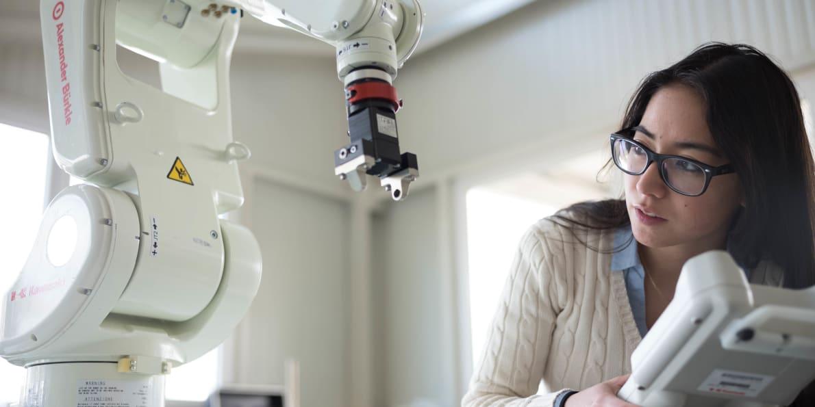 Frau steuert einen Roboterarm