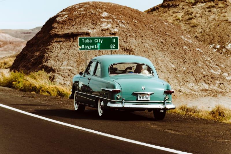 Image d'une vieille voiture roulant sur une route d'Arizona