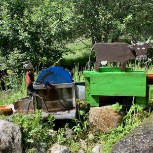 Une petie vache en bois fabriquée de manière artisanale mange du fourage. Elle est actionné par une petite roue à aube.