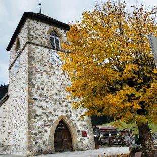 L'église de vers l'église au deuxième plan. Au premier plan se trouve un arbre aux couleurs d'automne.