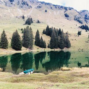 Le lac Retaud vu depuis le restaurant. Une barque est amarée en premier plan. quelques sapins et la montagne sont visibles au deuxième plan. Ceux-ci se réfléchissent à la surface du lac