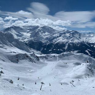 La vue depuis les Attelas sur les pistes de ski du domaines des 4 vallées. Les montagnes abondament enneigées se découpent sur un ciel bleu.