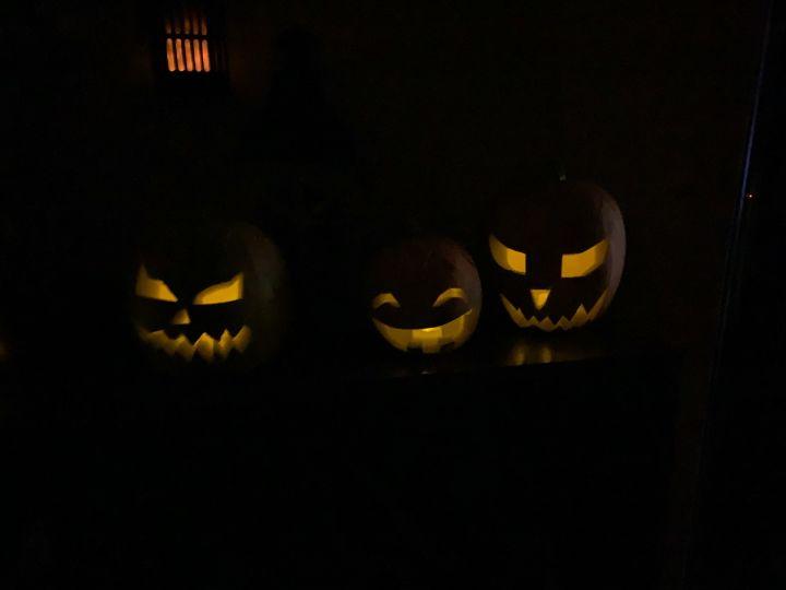 Three halloween pumpkins in the dark
