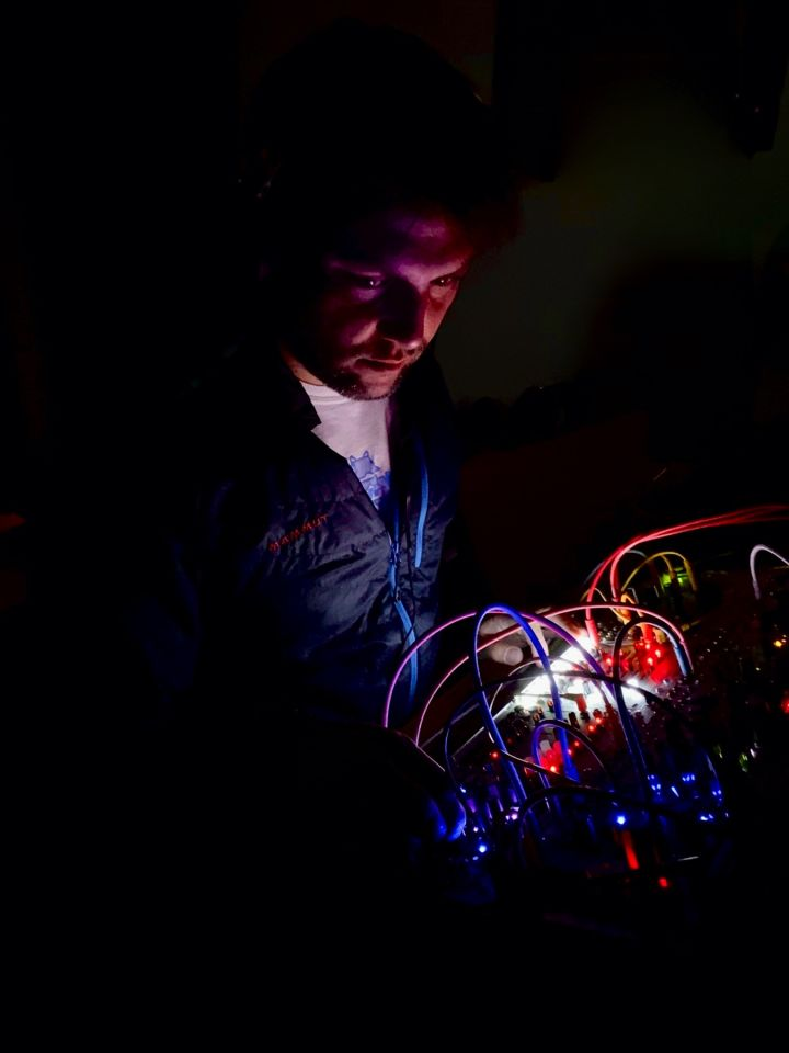 Photo of me in the dark. My face is lit by the leds of my eurorack system.