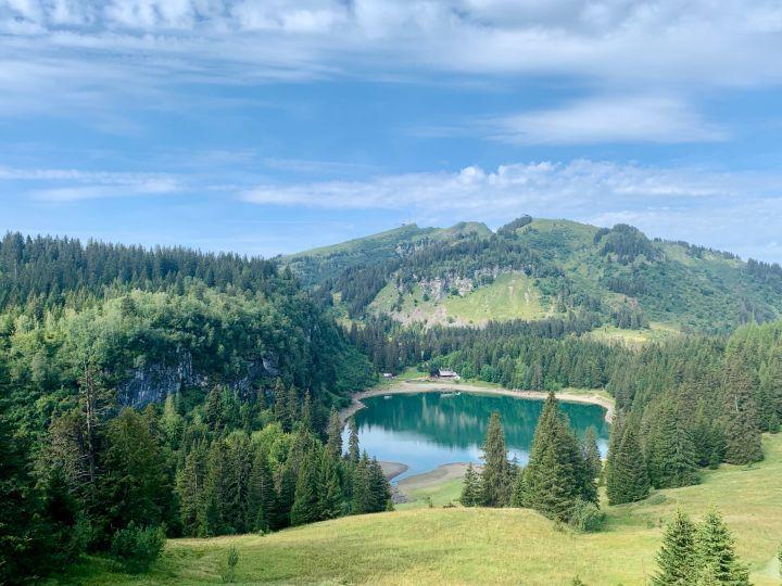 Le lac de Chavonnes en contre-bas avec ses reflets bleus-verts sous un ciel bleu magnifique. Sur la rive opposée se trouve le restaurant du lac. En arrière plan on peut voir le Grand Chamossaire.
