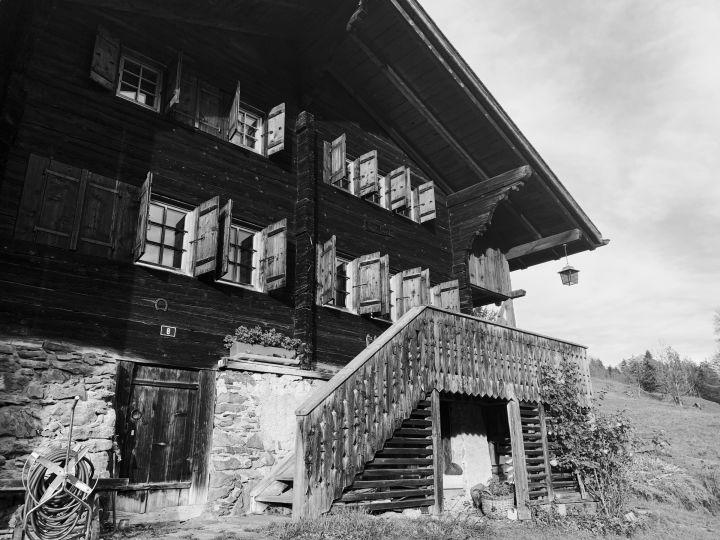 La photo est en noir et blanc. Un châlet typique en bois occupe les trois quart de la photo. Tout les volets sont ouvert à moitié. Une lanterne est suspendue à l'angle du toit et se détache sur le ciel.