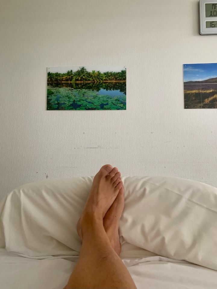 The wall of my hospital room. Below the image, we see my feet crossed in my bed