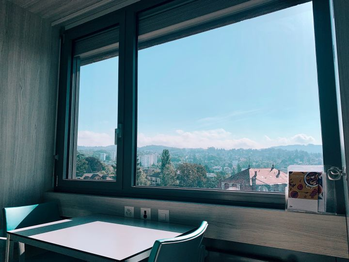 The view from my bed. We see a table with two chairs in front of the window. Through the window you can see the hill of Epalinge and the district of Chailly. The weather is sunny