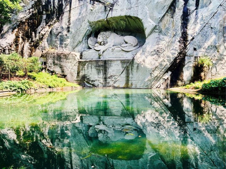 Löwendenkmal. A lion carved from a rock wall. He's got a spear stuck in his side. A shield with the Swiss harmonies is at its side. The lion is dying.