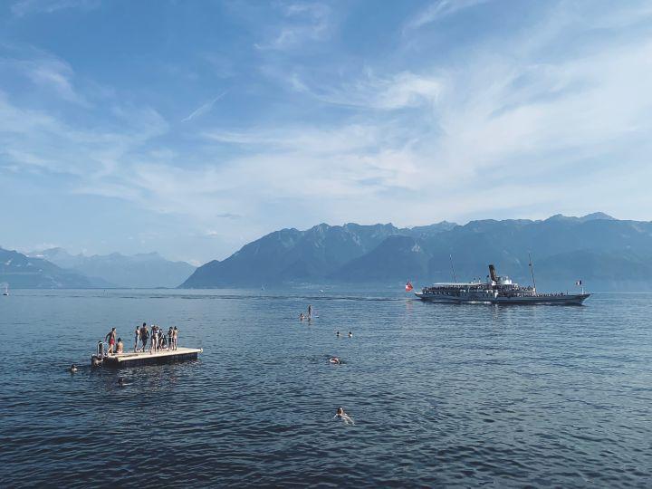 A la plage de Moratel, au bord du lac Léman. Au premier des enfants jouent sur le radeau de la plage sur le lac. Au deuxième plan le bateau à vapeur Montreux. En arrière plan, on voie le Chablais et les alpes savoyardes. La météo est radieuse